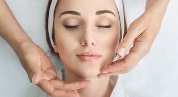 woman getting a facial massage during skin care treatment