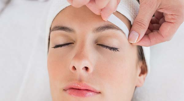 cosmetologist removing wax during a facial for the eyebrows